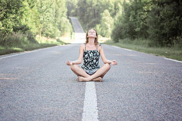 Donna che medita seduta in mezzo a una strada deserta