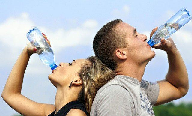 Donna e uomo bevono acqua dalla bottiglia