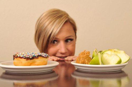 Ragazza che ha fame, indecisa tra una ciambella con cioccolato e una mela