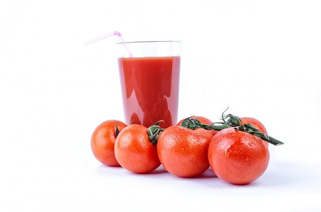 Succo di pomodoro in un bicchiere e quattro pomodori interi