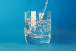 Bicchiere d'acqua su sfondo azzurro