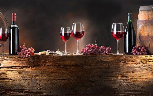 Bottiglie di vino rosso, grappoli d'uva e bicchieri di vino