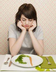 Ragazza triste guarda una sola carota nel suo piatto