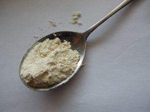 Cucchiaio colmo di proteine whey del siero di latte