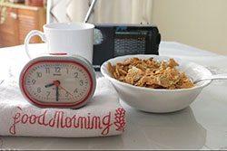 Sveglia vicino a ciotola con fiocchi di cereali