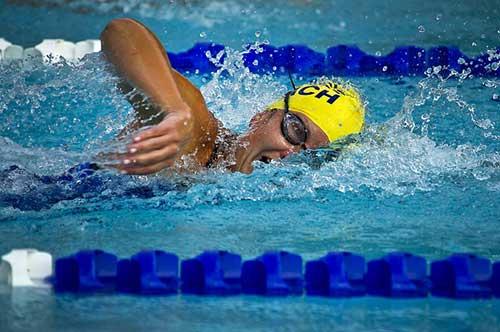 Atleta donna nuota a stile libero con cuffia gialla