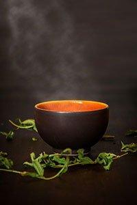 Tazza piena di tè verde bollente