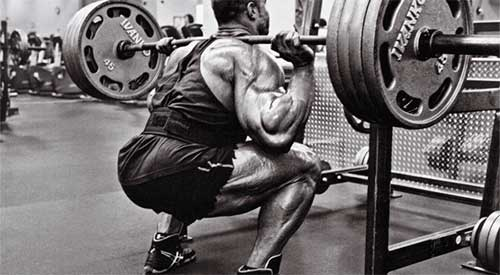 Bodybuilder esegue squats con pesi