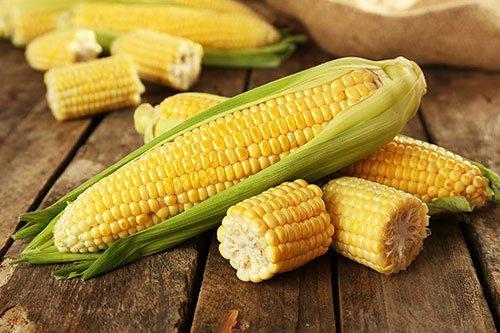 Pannocchie di mais su tavolo di legno